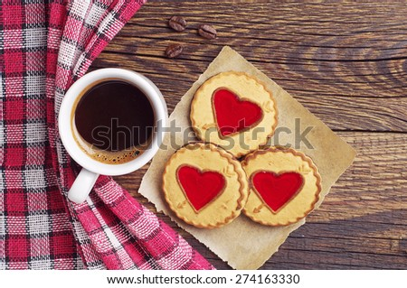 Cup of coffee and cookies with jam in shape of heart on wooden table, top view - stock photo