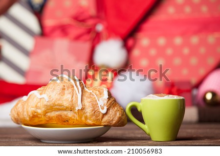 Cup of coffee and croissant on christmas background.