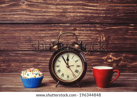 Cup of coffee and cupcake with alarm clock on wooden table. - stock photo