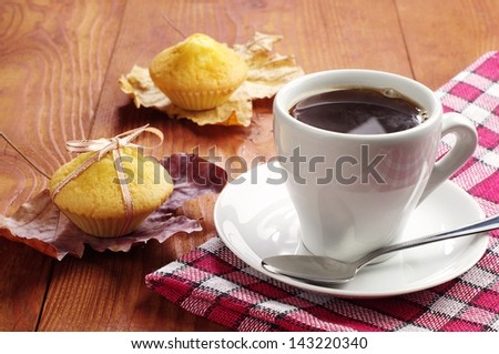 Cup of coffee and cupcakes on wooden table