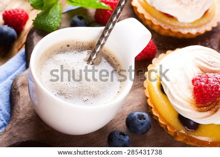Cup of coffee and delicious homemade tartlets served with lemon, lime curd cream, berries and meringue on old cutting board.  - stock photo