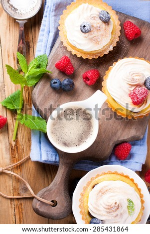 Cup of coffee and delicious homemade tartlets served with lemon, lime curd cream, berries and meringue, taken from above on old cutting board.  - stock photo