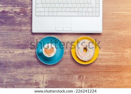 Cup of coffee and donut with notebook on a table. - stock photo