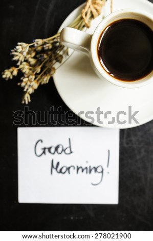 Cup of coffee and dried lavander flowers on the old wooden table - stock photo