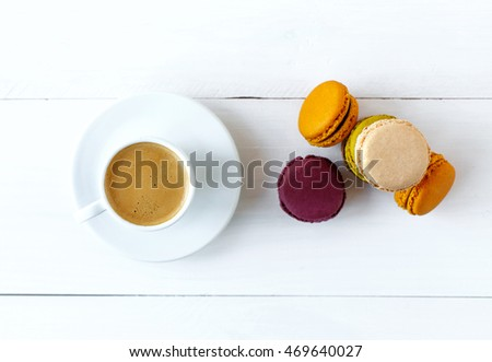 Cup of coffee and french macaron on an old wooden table.