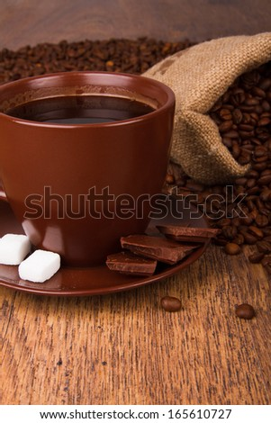 Cup of coffee and fresh coffee beans on a wooden background