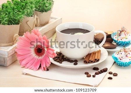 cup of coffee and gerbera  beans, cinnamon sticks on wooden table