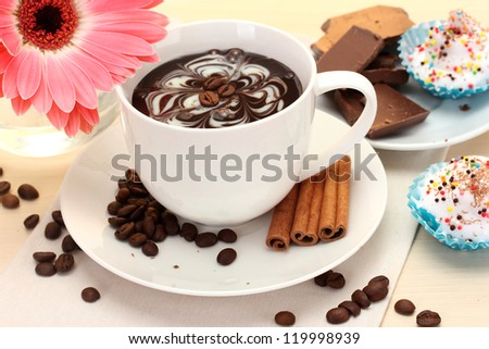 cup of coffee and gerbera, beans, cinnamon sticks on wooden table