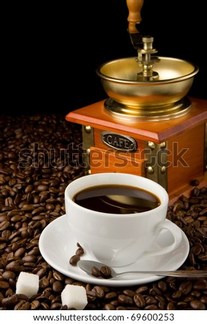 cup of coffee and gold grinder on beans - stock photo
