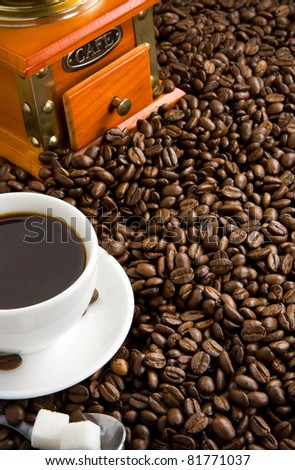 cup of coffee and grinder with roasted beans on straw - stock photo
