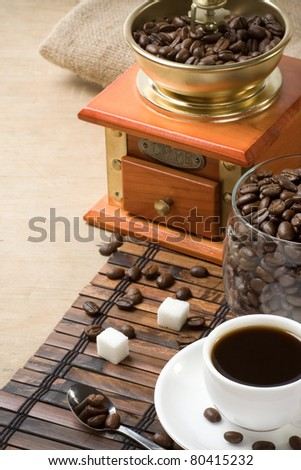 cup of coffee and grinder with roasted beans on wooden - stock photo