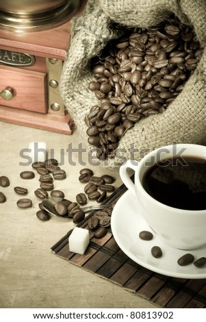 cup of coffee and grinder with roasted beans on wooden background - stock photo