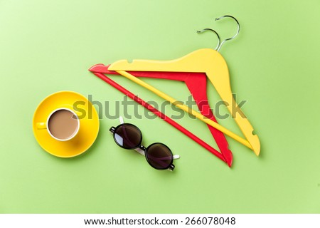 Cup of coffee and hangers with sunglasses on green background. - stock photo