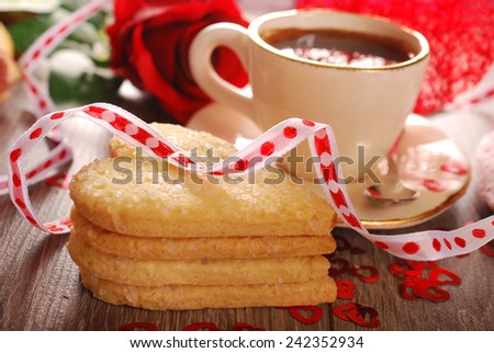 cup of coffee and heart shaped cookies with sugar for valentine on wooden table