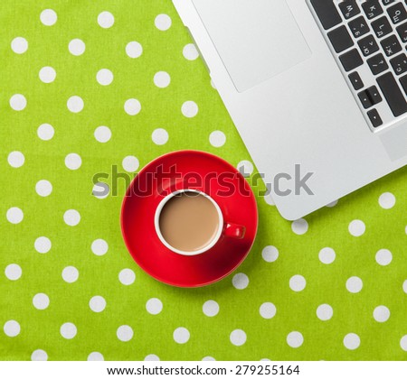Cup of coffee and laptop computer on green polka dot background - stock photo