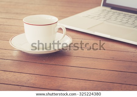 Cup of coffee and laptop computer on wooden background, warm retro style - stock photo