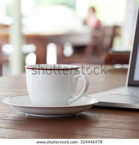 Cup of coffee and laptop computer on wooden table - stock photo