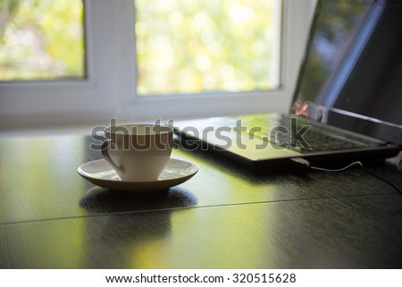 cup of coffee and laptop in front of the window