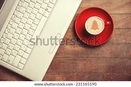 Cup of coffee and laptop on wooden table. - stock photo
