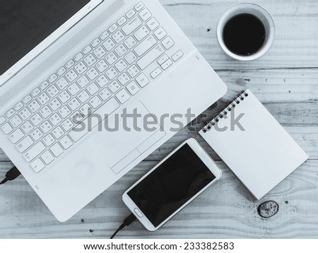 Cup of coffee and laptop on wooden table in mono tone color