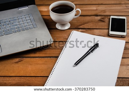 Cup of coffee and laptop on wooden table. Stock image.