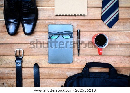 Cup of coffee and men accessories on old wooden background, Business themes - stock photo