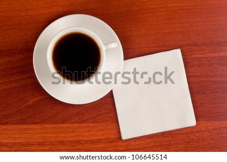 Cup of coffee and napkin on table - stock photo