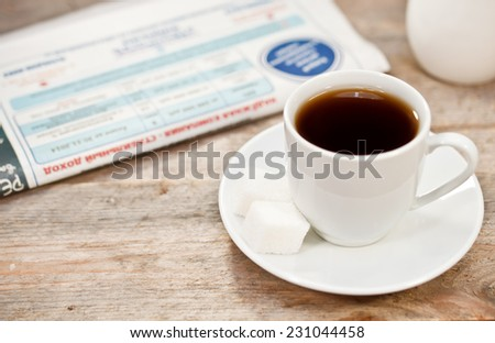 Cup of coffee and newspaper on a wooden table  - stock photo