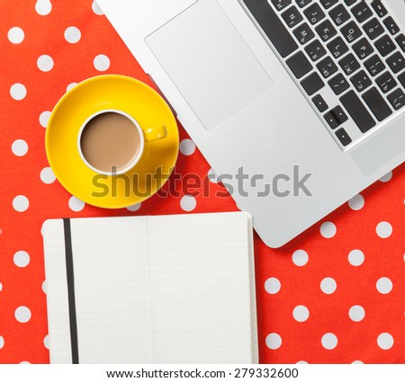 Cup of coffee and notebook near laptop computer on red polka dot background - stock photo