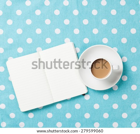 Cup of coffee and notebook on blue polka dot background. - stock photo