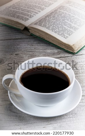 Cup of coffee and old book on a wooden table