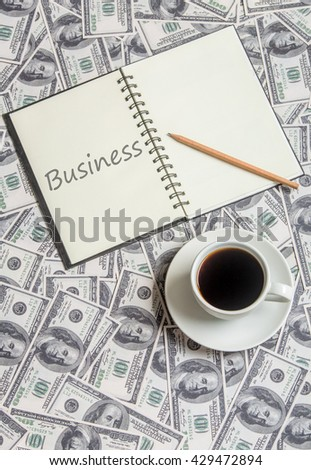 """Cup of coffee and open book with word """"business"""" - stock photo"""