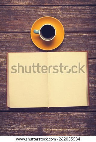 Cup of coffee and opened book on wooden background - stock photo