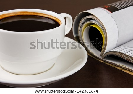 Cup of coffee and opened magazine on table