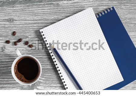 Cup of coffee and opened notepad on a wooden table, top view. Space for your text