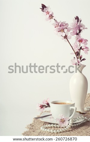 cup of coffee and pink cherry blossoms - stock photo