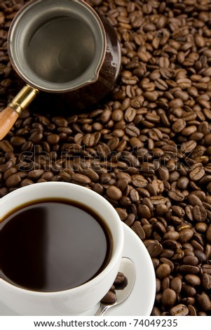 cup of coffee and pot on roasted beans as background - stock photo