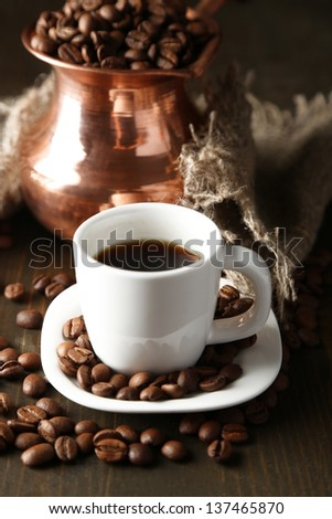 Cup of coffee and pot on wooden background