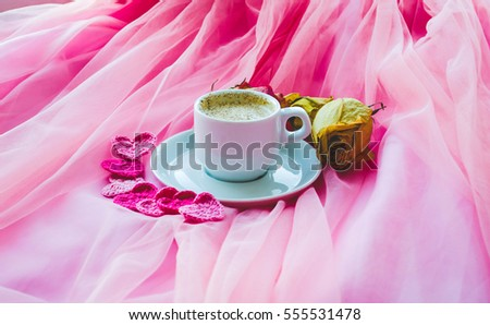 Cup of coffee and roses on pink background