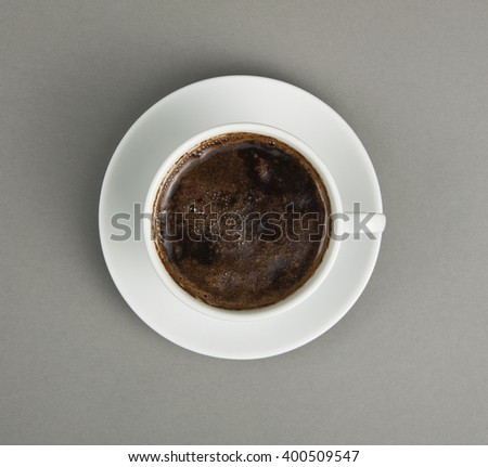 Cup of coffee and saucer on a gray background