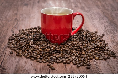 Cup of coffee and spilled coffee beans - stock photo