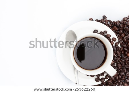 Cup of coffee and spoon on coffee beans. isolated on white. - stock photo