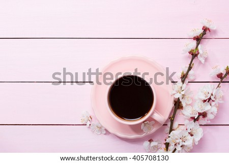 Cup of coffee and spring  flowers  on pink wooden table. - stock photo