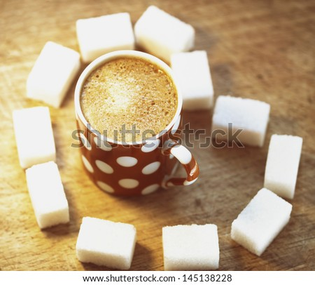 Cup of coffee and sugar cubes heart shape on wooden board - stock photo