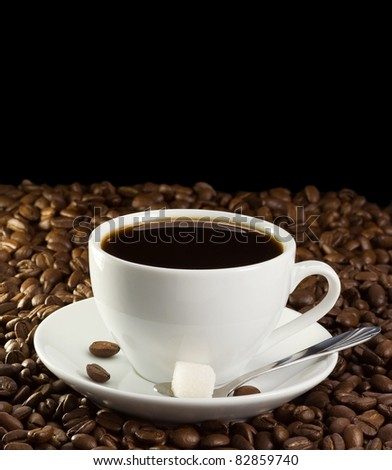 cup of coffee and sugar on beans isolated on black - stock photo