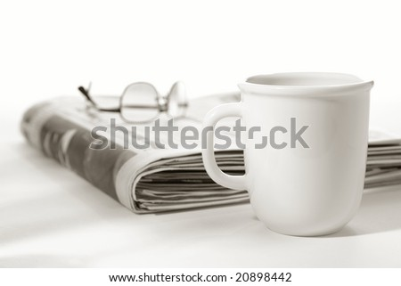 Cup of coffee and Sunday morning edition newspaper with glasses