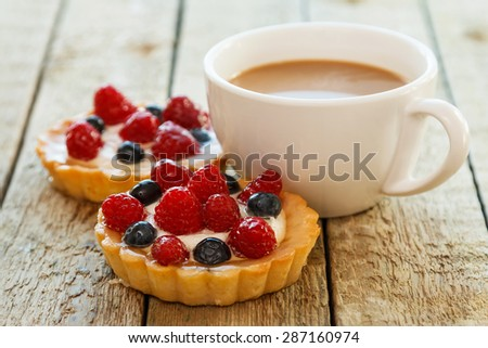 Cup of coffee and sweet cakes with berries on wooden table - stock photo