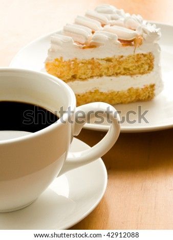 Cup of coffee and tasty cream cake with apricots. Shallow dof. - stock photo