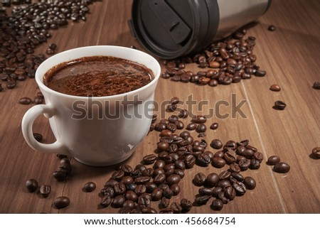 cup of coffee and Thermocup on the table - stock photo