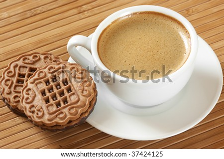 Cup of coffee and two cookies on wooden mat. - stock photo